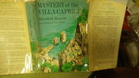 Mystery at the Villa Caprice in Blue & Green Color Dustjacket of 4 kids hiding behind a rock high on the Cliff watching a man climbing up the hill, First Edition stated. This is a rare signed book by the author with Name Betty. Darcy gets an Unexpected Tr