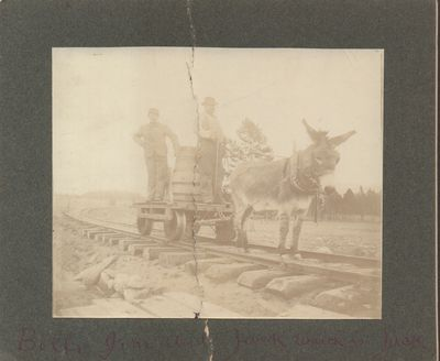 Good. Mounted gelatin silver print depicting a two men and a burro on railroad tracks. Photo print m...