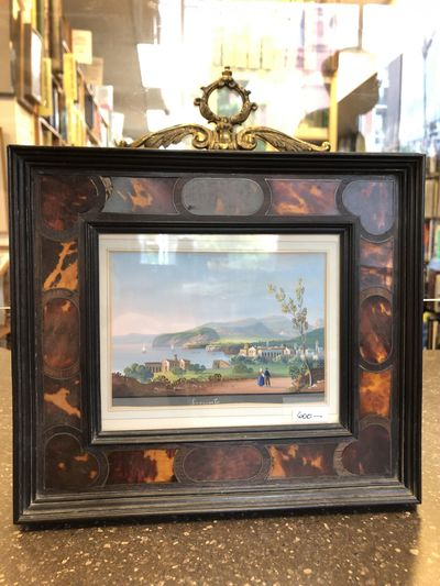 A framed painting of a seaside town landscape scene;