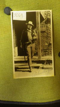 Signed photograph John Wayne   B/W  ,  Wayne is dressed in  Western attire with badge, scarf, Hat & Rifle at Sherrif's Office