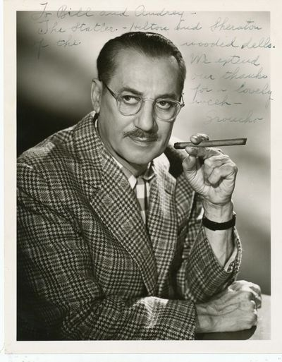 The iconic comedian is shown seated, holding a cigar in his raised left hand. He has inscribed,