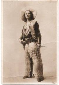 SEPIATONE STUDIO PHOTOGRAPH OF A COWBOY IN FULL REGALIA:  sheepskin chaps, ten-gallon hat, vest, bandanna, pistol belt, holster and pistol, and holding a small whip.