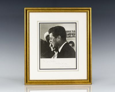 Photograph of President Kennedy smiling in profile, with the first lady pictured just behind him. Bo...