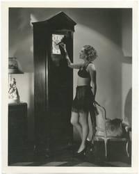 (Press photograph): Portrait of Astrid Allwyn setting a grandfather clock in her underwear