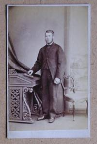 Carte De Visite Photograph: Portrait of a Man Standing Betwwen a Desk & Chair.