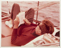 Color Photograph of the President lying on a sailboat, reading , presented to Evelyn Lincoln, the late Presdident's Secretary; with accompany Autograph Letter Signed from Senator Muskie, presenting the photograph; and the retained copy of Mrs. Lincoln's letter of thanks to Muskie