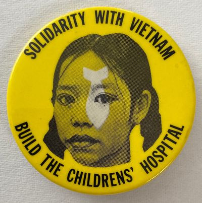 New York: mfg. by NG Slater, n.d.. 2.25 inch pin depicting a Vietnamese girl, a superimposed falling...