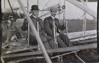 Photograph of Orville Wright with Major Albert B. Lambert seated in the Wright Flyer, 1910, signed by Orville Wright at the right area of the image by  Orville (Aviation) Wright - Signed - 1910 - from James Cummins Bookseller and Biblio.com