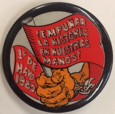 n.p.: , 1980. 1.75 inch diameter pin depicting hand grasping a red banner as it breaks free from sha...