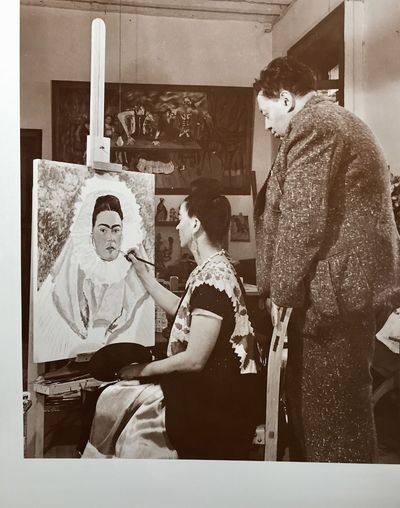 Large photo, 19x14.5n, on card stock paper, of Frida Kahlo, seated and painting, while Diego Rivera ...