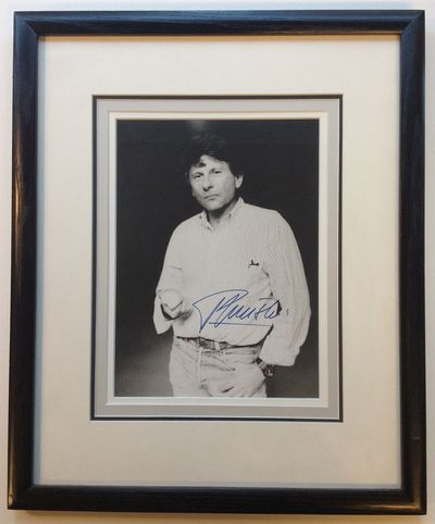 1985. unbound. 9 x 6.5-inch black-and-white photo of Polanski standing casually and facing the camer...